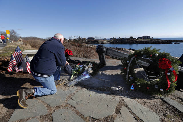 A man pays his respects to former President George H. W. Bush at a makeshift memorial across from Walker's Point, the Bush's summer home, Saturday, Dec. 1, 2018, in Kennebunkport, Maine. Bush died at the age of 94 on Friday, about eight months after the death of his wife, Barbara Bush. (AP Photo/Robert F. Bukaty)