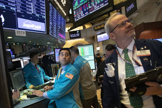 William Geier, Jr., left, and David O'Day work at the New York Stock Exchange, Tuesday, Dec. 11, 2018, in New York. Stock markets around the world spiked higher Tuesday after Wall Street rebounded amid hopes the U.S. and China are back negotiating over their trade dispute. (AP Photo/Mark Lennihan)