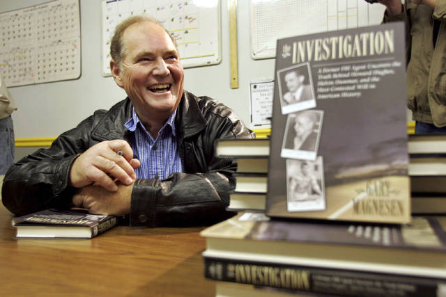 FILE - In this Nov. 10, 2005 file photo, Melvin Dummar smiles after signing copies of a book that Gary Magnesen had written about Dummar's claims that Howard Hughes left him a portion of the Hughes estate. Dummar, a delivery driver who falsely claimed that billionaire Howard Hughes left a handwritten will bequeathing him $156 million, has died in rural Nevada. Nye County Sheriff Sharon Wehrly said Dummar died Sunday, Dec. 9, 2018, under hospice care. He was 74. (Scott G. Winterton/Deseret Morning News via AP, File)