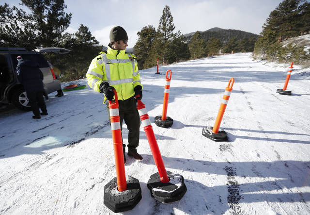 Park ranger Kevin Sturmer drags pylons up Trail Ridge Road to block access after an overnight snow was left unplowed in Rocky Mountain National Park Saturday, Dec. 22, 2018, in Estes Park, Colo. Roads were unplowed in the park because of a partial federal shutdown has been put in motion because of gridlock in Congress over funding for President Donald Trump's Mexican border wall. (AP Photo/David Zalubowski)