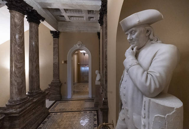 A statue of Benjamin Franklin is seen in an empty corridor outside the Senate at the Capitol in Washington on Thursday during a partial government shutdown. Chances look slim for ending the partial government shutdown any time soon. Lawmakers are away from Washington for the holidays and have been told they will get 24 hours' notice before having to return for a vote.