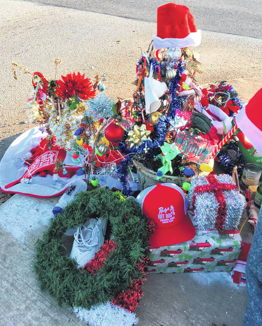 "Christmas decorations and donations surround the ""Christmas weed"" in Toledo on Dec. 18. On Friday, the weed disappeared."
