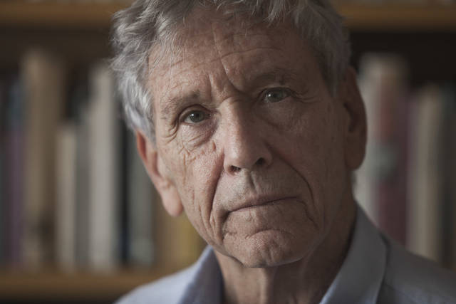 FILE - In this Nov. 4, 2015 file photo, Israeli writer Amos Oz poses for a photo at his house in Tel Aviv, Israel. Israeli media said Friday, Dec. 28, 2018 that renowned Israeli author Amos Oz has died at the age of 79. Oz, author of novels, prose and a widely acclaimed memoir, had suffered from cancer. Oz won numerous prizes, including the Israel Prize and Germany's Goethe Award, and was a perennial contender for the Nobel Prize in literature. (AP Photo/Dan Balilty, File)
