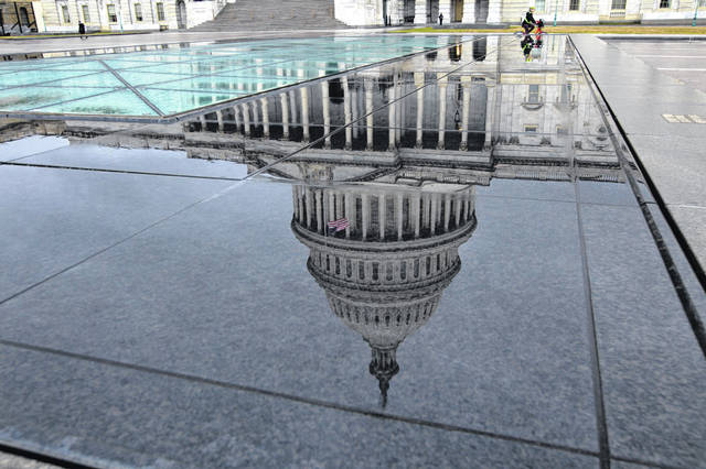 The U.S. Capitol is seen reflected after rain in Washington, Friday, Dec. 21, 2018. The Republican-led House approved funding for President Donald Trump's border wall in legislation that pushes the government closer to a partial government shutdown. The bill now goes to the Senate.