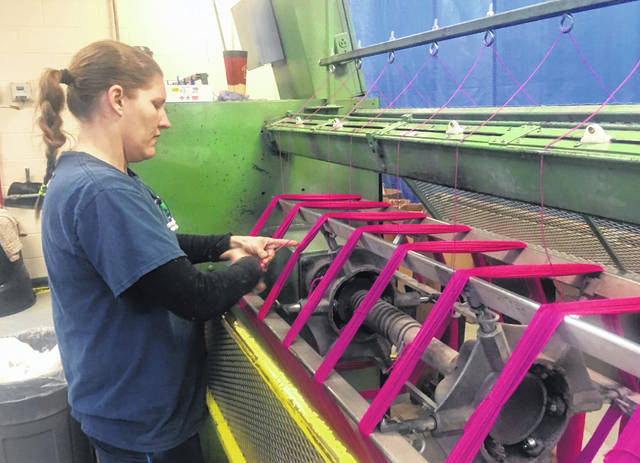 Debbie McDermott's daughter, Jamie Sparks, ties freshly-spun yarn into skeins in October. Sparks' raising of two sheep for a 4-H project inspired her mother to establish Stonehedge Fiber Mill in East Jordan, Mich., on the family's 165-year-old farm in 1999.
