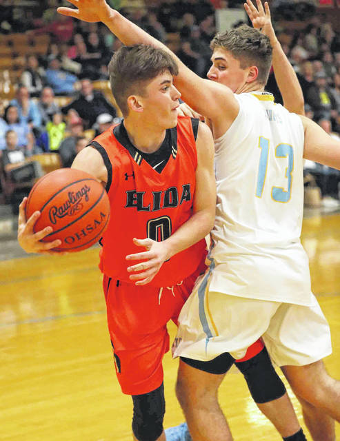 Elida's Matt Fish tries to make a pass from under the basket as he is defended by Bath's Jonah Wauben during Friday night's Western Buckeye League game at Bath.