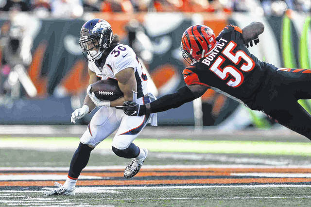 Denver Broncos running back Phillip Lindsay (30) breaks away from Cincinnati Bengals outside linebacker Vontaze Burfict (55) in the first half of an NFL football game, Sunday, Dec. 2, 2018, in Cincinnati. (AP Photo/Gary Landers)