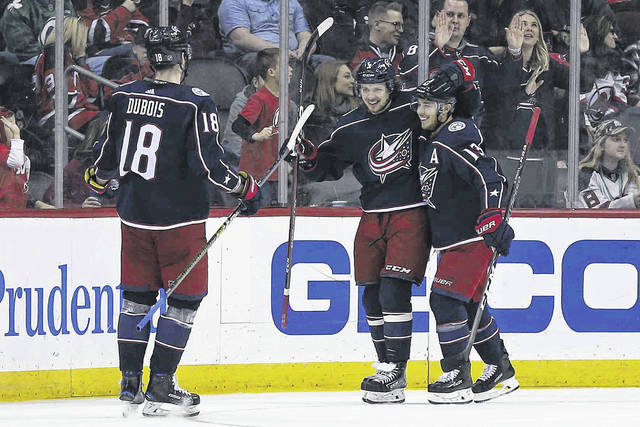 Columbus Blue Jackets' Artemi Panarin celebrates scoring a goal with teammates Blue Jackets' Cam Atkinson (13) and Blue Jackets' Pierre-Luc Dubois (18) during the second period of an NHL hockey game against the New Jersey Devils on Sunday, Dec. 23, 2018, in Newark, N.J. (AP Photo/Adam Hunger)