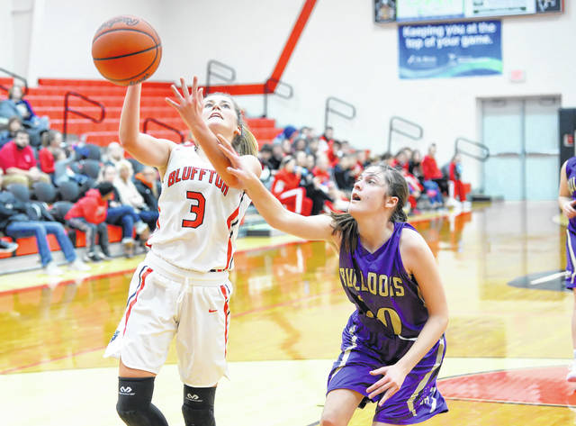 Bluffton's Laykin Garmatter puts up a shot against Ada's Kirsten Poling during Thursday night's Northwest Conference game at Bluffton High School.