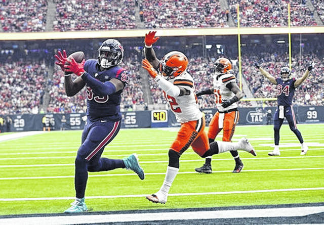 Houston Texans tight end Jordan Thomas (83) makes an 11-yard touchdown catch in front of Cleveland Browns free safety Jabrill Peppers (22) during the first half of an NFL football game, Sunday, Dec. 2, 2018, in Houston. (AP Photo/Sam Craft)