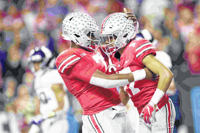 Ohio State wide receiver Chris Olave, right, is congratulated by quarterback Dwayne Haskins (7) after catching a touchdown pass during the second half of the Big Ten championship NCAA college football game against Northwestern, Saturday, Dec. 1, 2018, in Indianapolis. (AP Photo/AJ Mast)