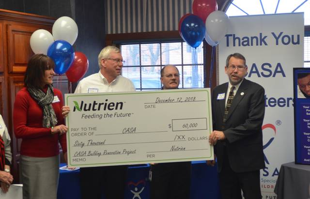 Nutrien representatives — Director of HR Business Relations Danielle Good, Training Manager Tim Weitz and General Manager Todd Sutton — present a $60,000 check to Crime Victim Services Executive Director David Voth.