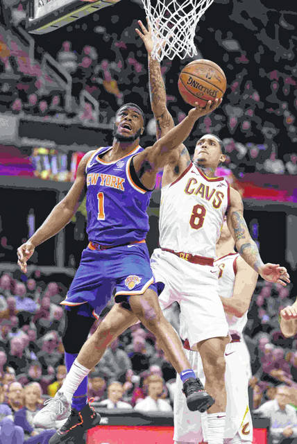 New York Knicks' Emmanuel Mudiay (1), from Congo, drives to the basket against Cleveland Cavaliers' Jordan Clarkson (8) in the second half of an NBA basketball game, Wednesday, Dec. 12, 2018, in Cleveland. The Cavaliers won 113-106. (AP Photo/Tony Dejak)