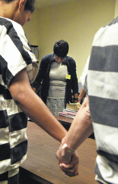 """Jean Foy holds hands with female inmates during a morning prayer at the Allen County jail recently. """"The Church Ladies,"""" as people call them, have been coming to the jail weekly to offer a message of hope to inmates for decades."""