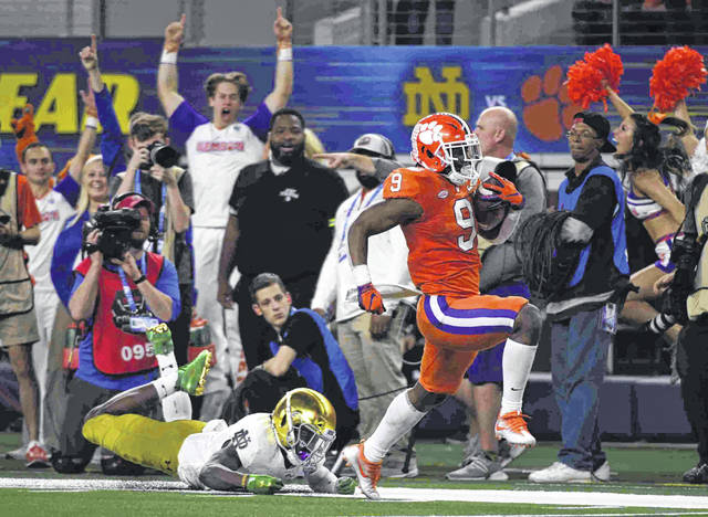 Notre Dame safety Jalen Elliott, left, is unable to stop Clemson running back Travis Etienne (9) from reaching the end zone for a touchdown in the second half of the NCAA Cotton Bowl semi-final playoff football game, Saturday in Arlington, Texas.
