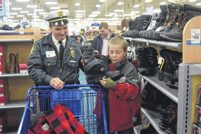 Lima Police Chief Kevin Martin helps Skylin Shappell load a pair of boots into a shopping cart.