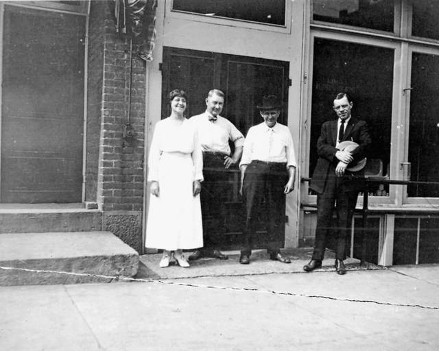 Lou King, bookkeeper, owners Charles C. Cowle and Charles M. Cantieny, and an unknown salesman pose for a photo, likely in front of the East Spring Street building. The photo is undated.