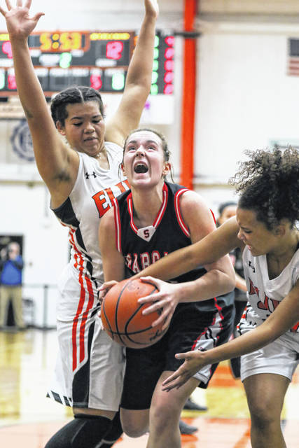Spencerville's Abbygayle Satterfield attempts to go up for a shot against Elida's Alissa Cuffy, left, and Amiah Jones during Tuesday night's gmae at the Elida Fieldhouse.