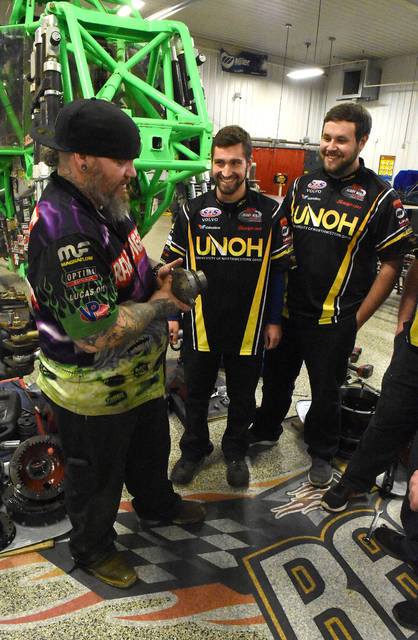 Michael Osborne, left, Grave Digger crew chief, talks shop with UNOH students, John Hartman and Brenden Rassel, during a pit stop at UNOH on Tuesday. Two of the world famous Grave Digger and El Toro Loco Monster Jam trucks are traveling through Lima and made a quick pit stop at the University of Northwestern Ohio S&S Volvo Motorsports Racing Complex. UNOH is able to provide the perfect indoor space for both trucks to make needed repairs before moving on to their next event in Dayton.