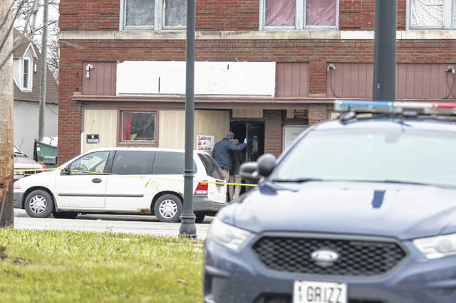 Investigators from the Lima Police Department examine the crime scene at 904 S. Main St. after one person was killed and three injured after a shooting at 4 a.m. Saturday morning.     Levi A. Morman | The Lima News