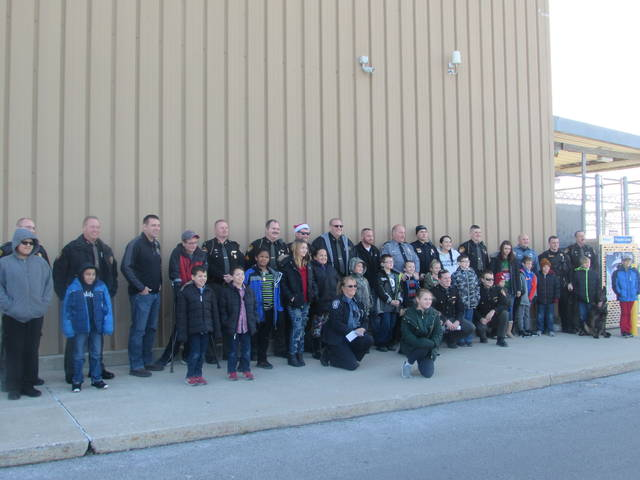 Putnam County Sheriff's Deparment and Putnam County Sheriff's Police Association members pose with youth as part of Saturday's Shop With A Cop event.