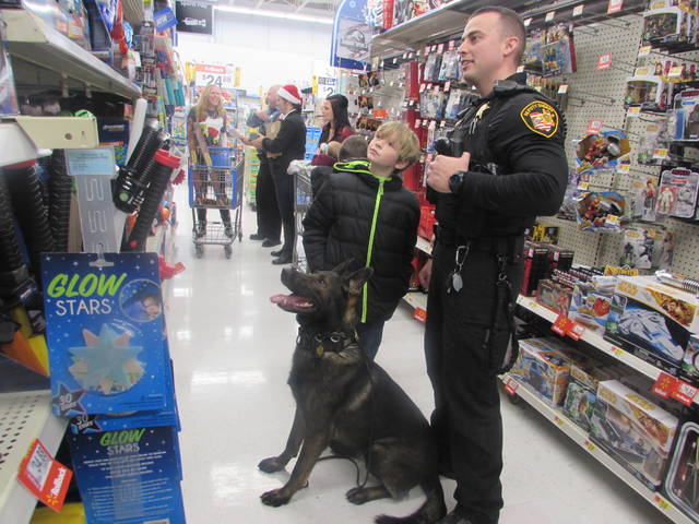 Zahnder Boggs, 9, shops for toys Saturday with the help of Troy Stevenson, Putnam County Sheriffs Department deputy and his K9 Nero.