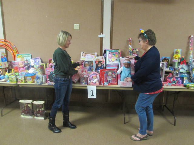 From left are Phyllis Macke, thrift store board treasurer, and Becky Diemer, Toys For Tots toy giveaway co-director, looking at toys for children.