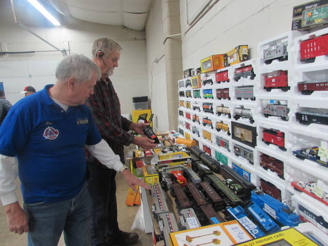 From left are Joe Painter, train show volunteer, and John Hile, of Churubusco, Indiana, looking at trains during Saturday's show at Allen County Fairgrounds.