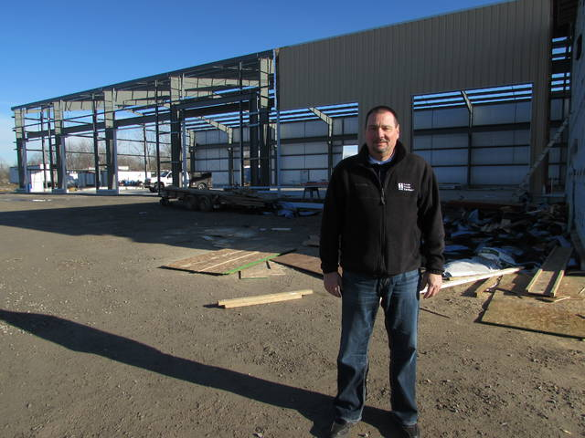 Joe Recker, Kalida Truck Equipment co-owner, stands next to an 18,000-square foot new building that is being built as a service and parts building for the business.