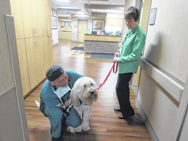 Scott Watamura, Lima Memorial Hospital anesthesiologist, pets therapy dog Max, 7, owned by Helen Bibler, right.