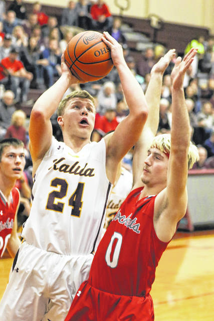 Kalida's Evan Roebke puts up a shot against Pandora-Gilboa's Walker Macke during Tuesday night's Putnam County matchup at Kalida.