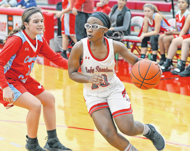 Lima Senior's Nakiya Sigman drives against Lima Central Catholic's Erin Mulcahy during Saturday's game at Lima Senior High School.