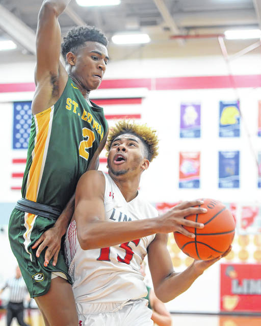 Lima Senior's Jamir Simpson goes up for a shot against Lakewood St. Edward's Montorie Foster during Saturday night's Kewpee Holiday Classic at Lima Senior High School.