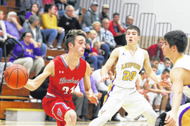 Pandora Gilboa's Nick Norton tries to find a pass against the defense of Leipsic's Drew Liffick (20) and Tyler Heigel during the Putnam County League game on Thursday night at Leipsic.