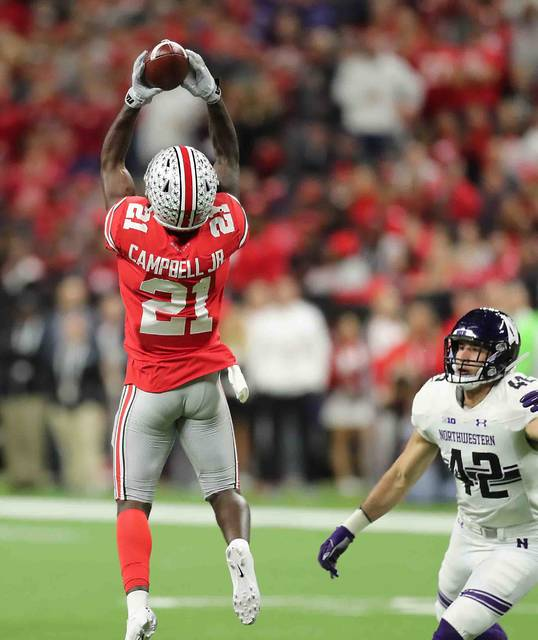 Ohio Statewide reciever Parris Campbell Jr. goes up high for a catch over Northwestern linebacker Paddy Fisher in the first half at Lucas oil Field during the Big Ten Championship game Saturday.