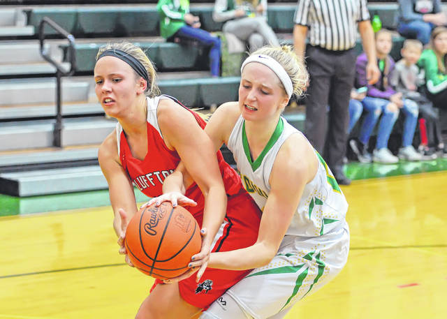Bluffton's Katie Prater, left, and Ottoville's Quinley Schlagbaum fight for a loose ball during Saturday's game at Ottoville High School. See more girls basketball photos at LimaScores.com.