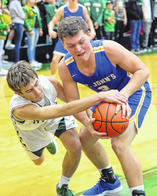 Ottoville's Joseph Miller, left, and Lucas Metcalfe of Delphos St. John's fight for a loose ball during Saturday night's game at L.W. Heckman Gymnasium.