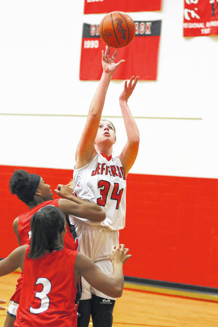 Delphos Jefferson's Brooke Brinkman goes to the basket against the defense of Perry's Tia Barfield and Zierra Thompson (3) on Wednesday night at Delphos Jefferson.