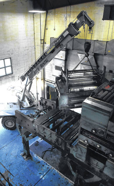 A crane is used to remove the upper tier of The Lima News printing press during the dismantling and removal on Friday.