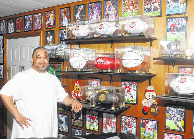 Lima resident Robert Phillips stands in front of some of his Ohio State autographed photos and other collectables.
