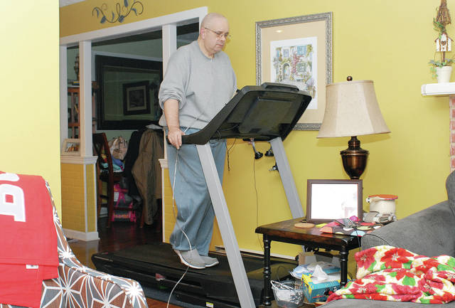 Grage Couch walks on a treadmill at his Sidney home Saturday, Dec. 29. He has lost 100 pounds so he can be eligible to receive a double lung transplant.