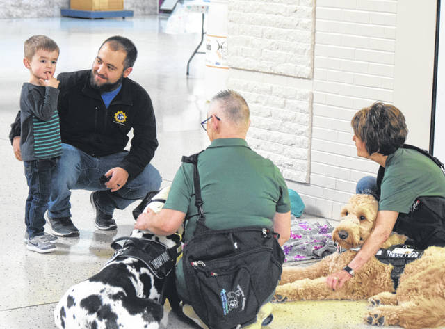 Max Capotosto and his dad Jacob, visit with the therapy dogs from Welcome Waggers at a Sensitive Santa event at the Lima Mall.