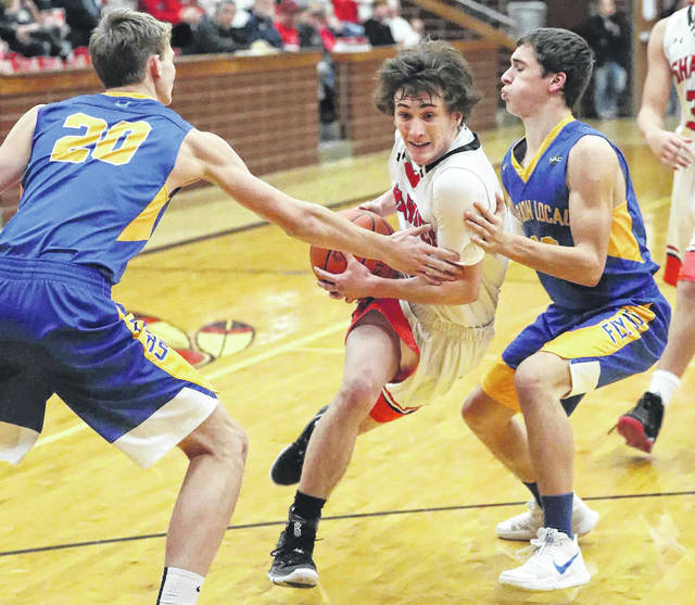 Shawnee's Justin Behnke drives against Marion Local's Nick Tangerman, left, and Matt Rethman during Saturday night's game at Lappin Gymnasium.