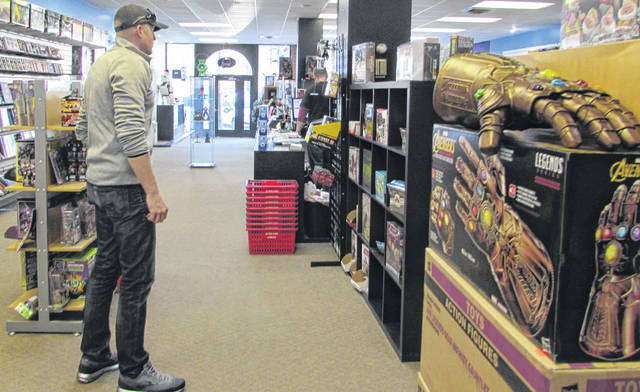 Eric Devers looks at merchandise at Alter Ego Comics on Lima's North Main Street on Wednesday. Owner Marc Bowker said 40 percent of his business comes from shopping in the store, with the rest coming online.