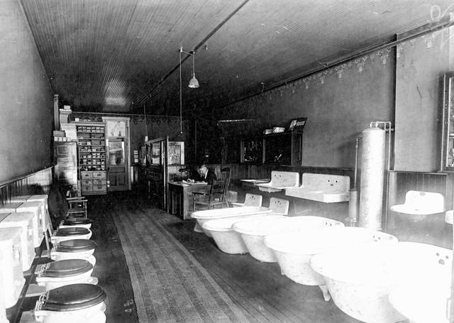 Toilets, bathtubs and sinks are lined up for customers at the company showroom, 125 E. Spring St. One of the owners is seated at the desk. The photo is undated.