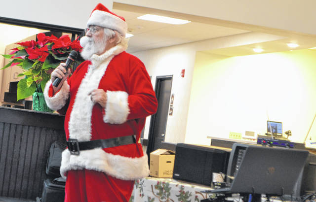 Robert J. Brown Sr. sings as Santa Claus for a crowd at the Springs of Lima on Eastown Road on Dec. 16. The holiday season brings plenty of opportunities to step in for the season's prime gift-deliverer.