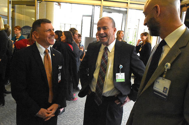 Dr. David Cohn, left, Dr. Chris Rhoades, and Bob Baxter, president, Mercy Health converse after the St. Rita's Medical Center & the James affiliation announcement on Wednesday morning at St. Rita's Cancer Center. Craig J. Orosz | The Lima News