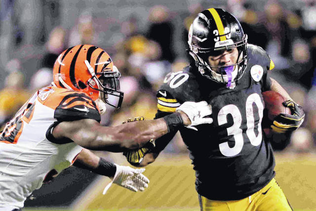 Pittsburgh Steelers running back James Conner (30) runs away from Cincinnati Bengals strong safety Shawn Williams (36) in the third quarter of an NFL football game against the Cincinnati Bengals, Sunday, Dec. 30, 2018, in Pittsburgh. (AP Photo/Gene J. Puskar)