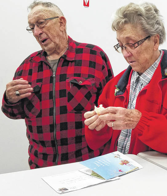 Reva Leach, 82, right, holds an anonymous card that contained a $1,000 donation as her husband, the Rev. James Leach, 82, talks about the gift Monday.