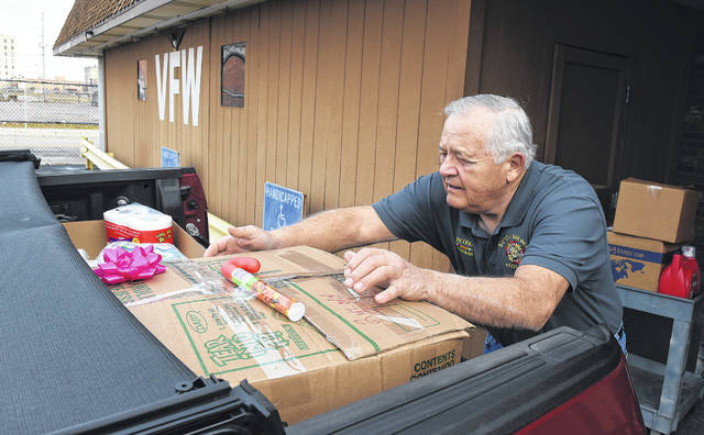 Butch Brewer, the Commander of Lima VFW Post 1275, loads Christmas gifts into his truck for needy veterans in Lima on Wednesday morning.